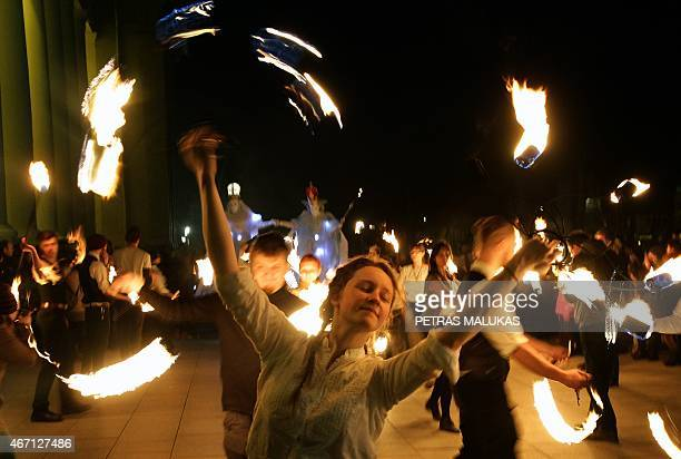 A woman performs with fire during the Spring Equinox Celebrations in Vilnius on March 20 2015 AFP PHOTO / PETRAS MALUKAS