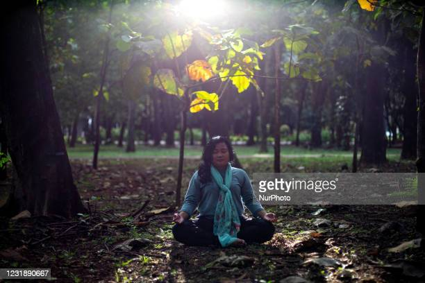 Woman performs Yoga after work hours at the Gelora Bung Karno sports complex, Jakarta March 23, 2021. The Covid-19 pandemic has made people find...
