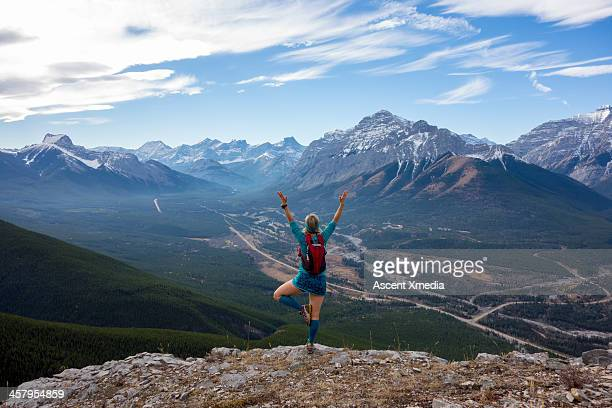 Woman performs yoga move on mountain ridge crest