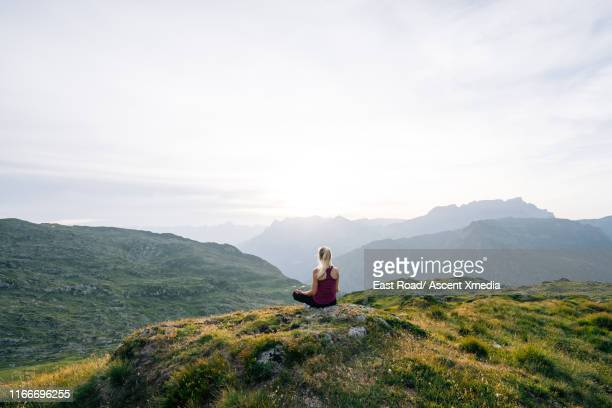 woman performs yoga moves on mountain summit - paradise stock pictures, royalty-free photos & images