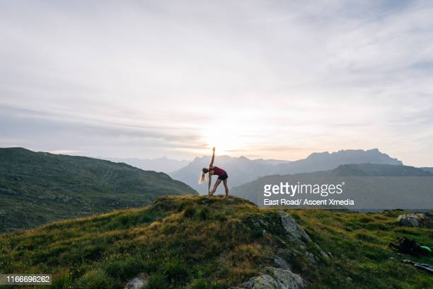 woman performs yoga moves on mountain summit - image stock pictures, royalty-free photos & images