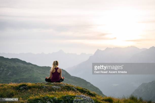 woman performs yoga moves on mountain summit - wellbeing stock pictures, royalty-free photos & images