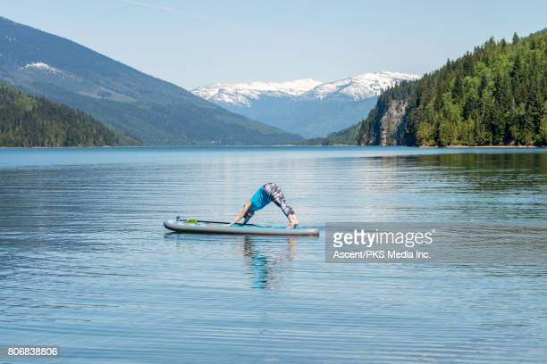 Woman performs yoga on stand up paddleboard, mountain lake