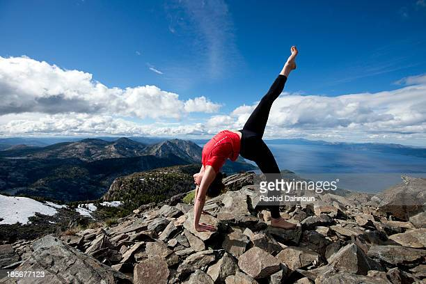 A woman performs yoga on top of Mount Tallac overlooking Lake Tahoe on a beautiful afternoon near South Lake Tahoe, CA.