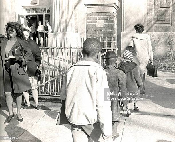 A woman perhaps a teacher or parent leads four young African American students into the school building during the school busing program implemented...