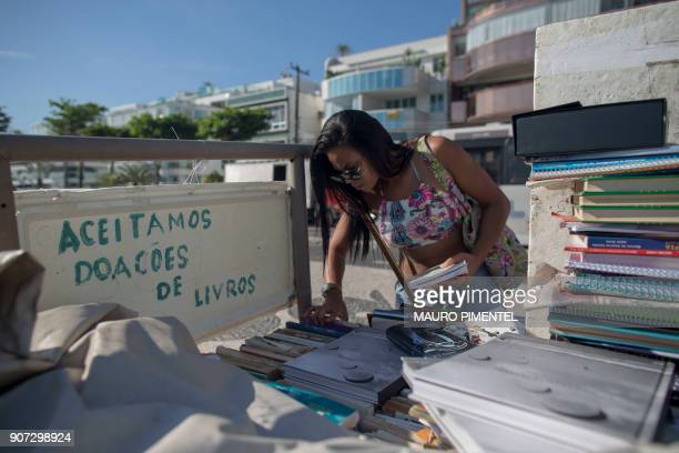 A woman peruses books next to a sign that reads 'We accept donations of books' at a stand set up by Marcio Mizael Matolias an artist who lives inside...