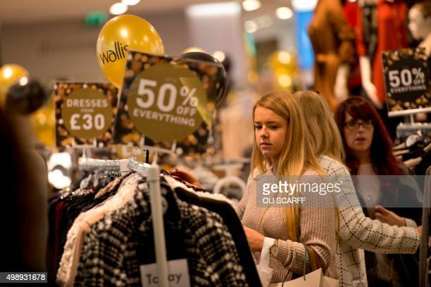 A woman peruses discounted clothing for sale in a shop in the Trafford Centre shopping mall on 'Black Friday' in Manchester northern England on...