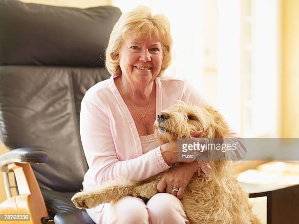 woman petting dog - labradoodle stock photos and pictures