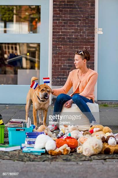 woman petting dog wearing dutch flags - merten snijders stockfoto's en -beelden