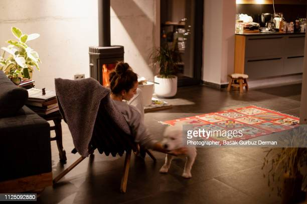 A woman petting her dog in front of a stove in a cozy living room