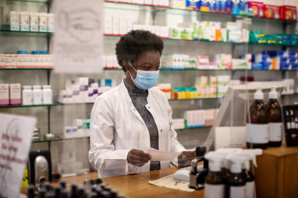 woman pharmacist with face mask working in a drug store picture id1251482289?k=6&m=1251482289&s=612x612&w=0&h=9 KcV1s5pCtCCDgLX zHZoCGoSHvLzVw4b5J3oRG1yk=