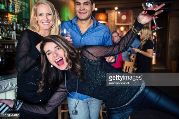 Woman photobombing in front of coworkers party in a bar.