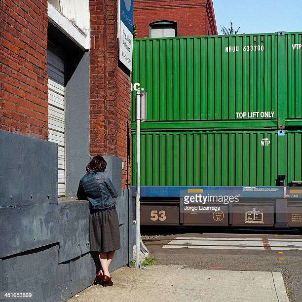 CONTENT] Woman photographed with back to camera standing close to a passing train while leaning on building texting on phone She is drressed in skirt...