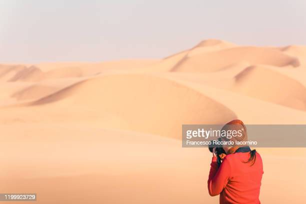 woman photographer in the desert, shooting at sand dunes - namib naukluft national park stock pictures, royalty-free photos & images