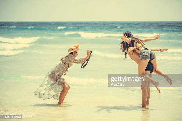 woman photographer working with couple on the beach - long dress stock pictures, royalty-free photos & images