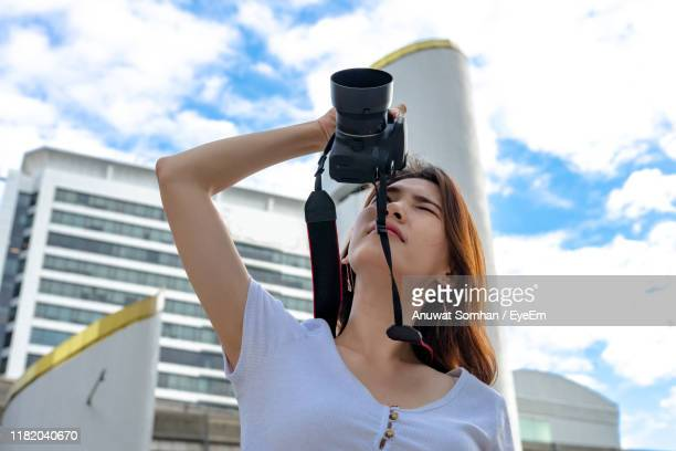woman photographing against sky - anuwat somhan stock photos and pictures