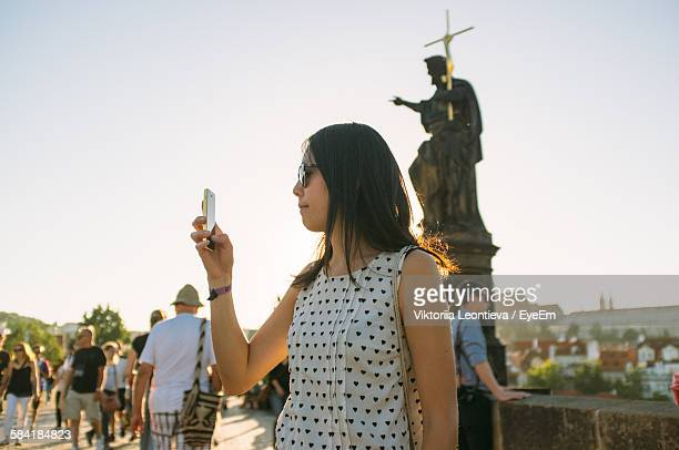 Woman Photographing At Charles Bridge Against Sky
