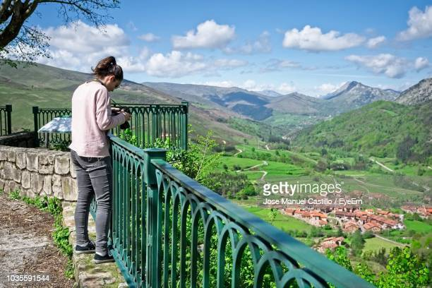 Woman Photographing At Railing Against Mountains