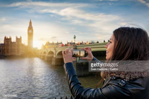 woman photographing big ben through mobile phone in city - westminster bridge stock pictures, royalty-free photos & images