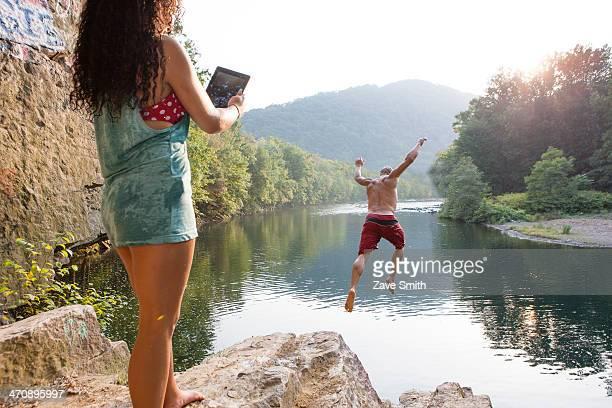 Woman photographing boyfriend jumping from rock ledge, Hamburg, Pennsylvania, USA