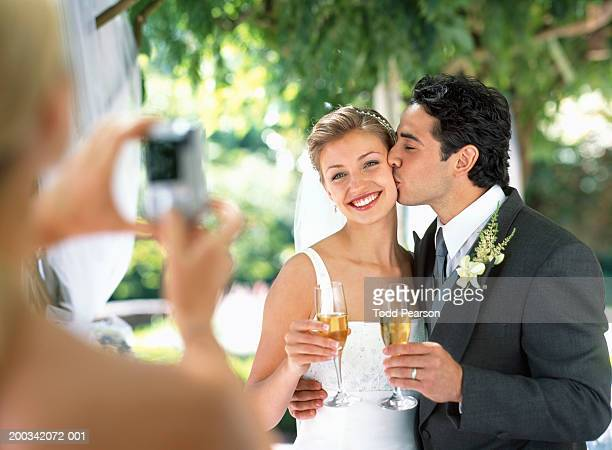 Woman photographing bride and groom drinking champagne