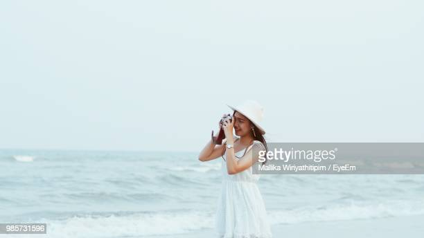 Woman Photographing By Sea Against Clear Sky