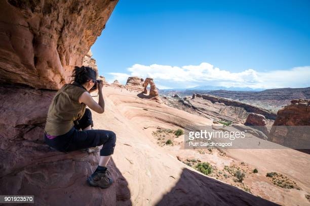 A Woman Photographing Delicate Arch