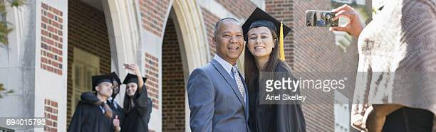 Woman photographing father and daughter with cell phone at graduation