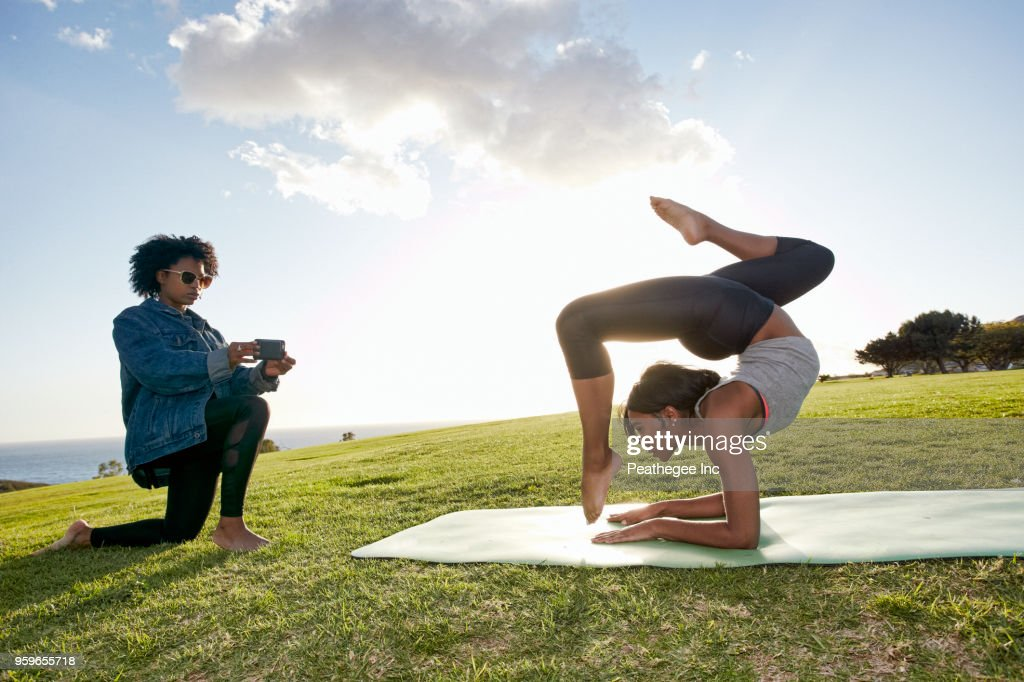 woman photographing female friend doing yoga : Stock-Foto