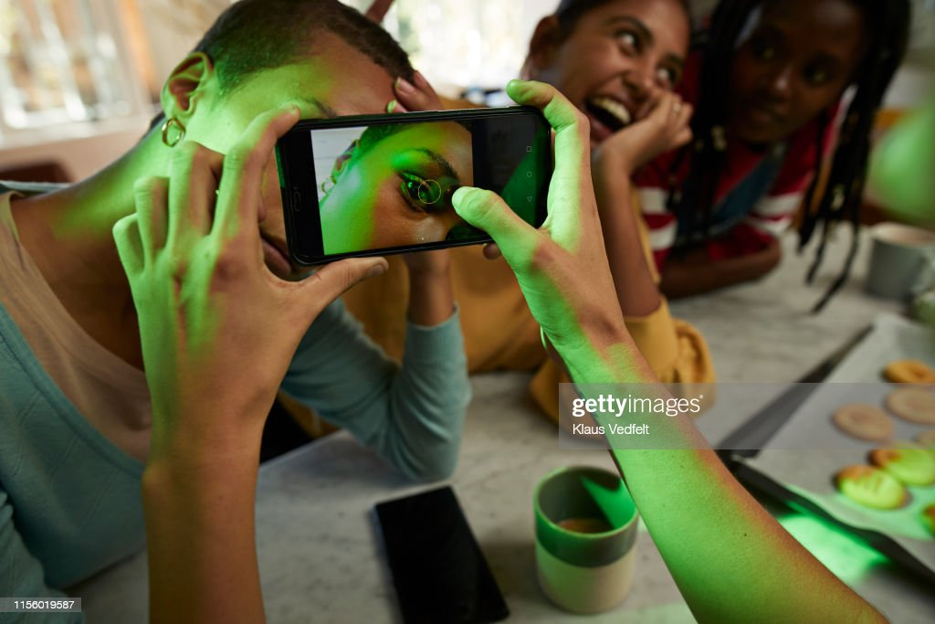 Woman photographing female friend's eye on phone : Stock Photo