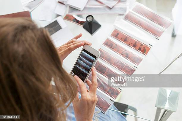 Woman photographing film strips with her mobile phone