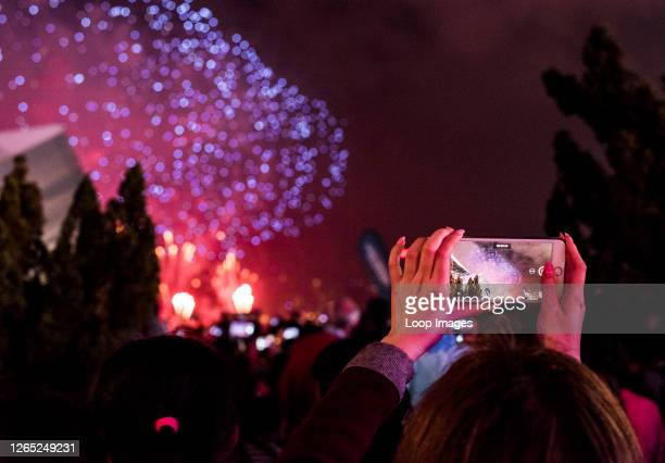 Woman photographing fireworks using smartphone during Chinese New Year celebrations in Kowloon in Hong Kong