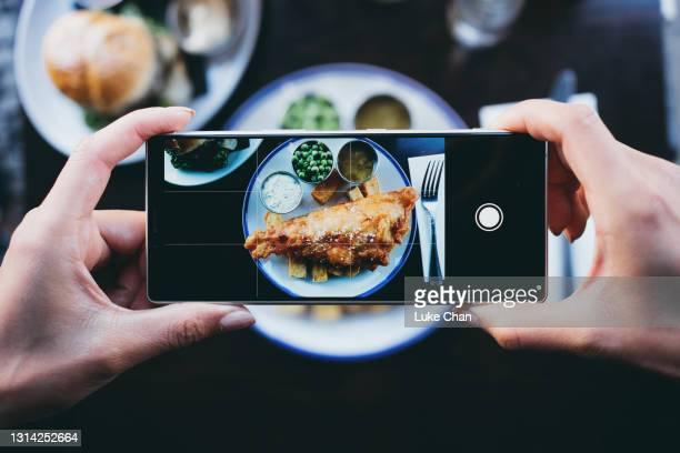 スマートフォン付きレストランで魚やチップスを撮影する女性 - モバイル撮影 ストックフォトと画像