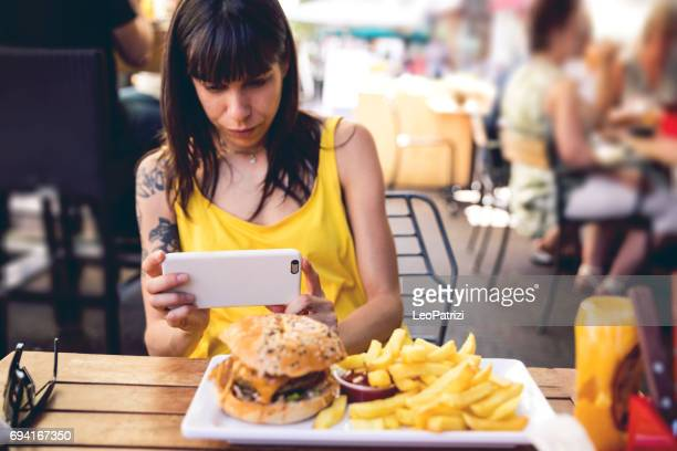 Woman photographing food at restaurant