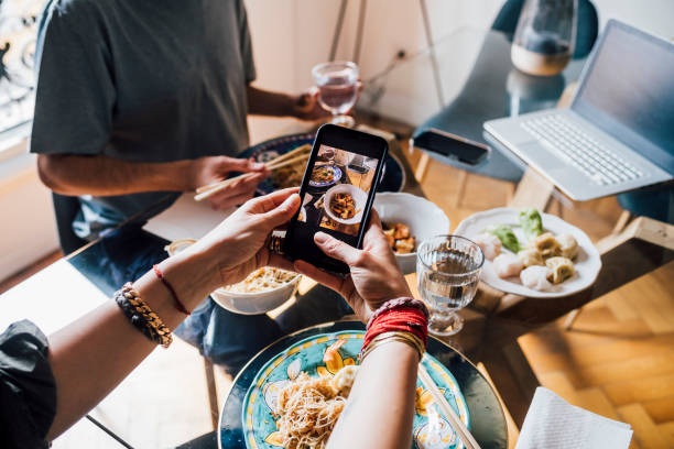 Woman photographing food through smart phone with man in background at dining table