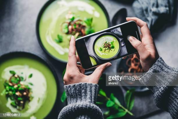 frau fotografiert frische grüne suppe - gourmet küche stock-fotos und bilder