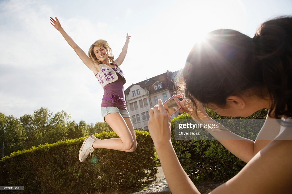 Woman photographing friend jumping : Stockfoto