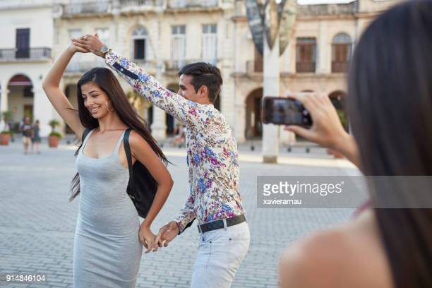 Woman photographing friends dancing in city