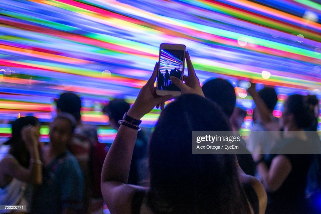 Woman Photographing Friends Dancing Through Mobile Phone Against Multi Colored Lights In Club : Stock Photo