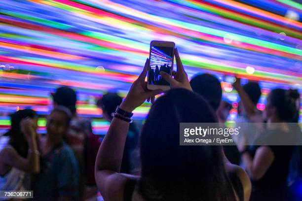 Woman Photographing Friends Dancing Through Mobile Phone Against Multi Colored Lights In Club