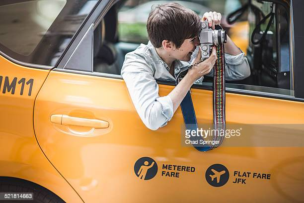 Woman photographing from yellow taxi, New York, US