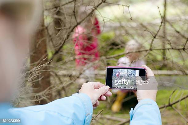 Woman photographing girls behind tree branches