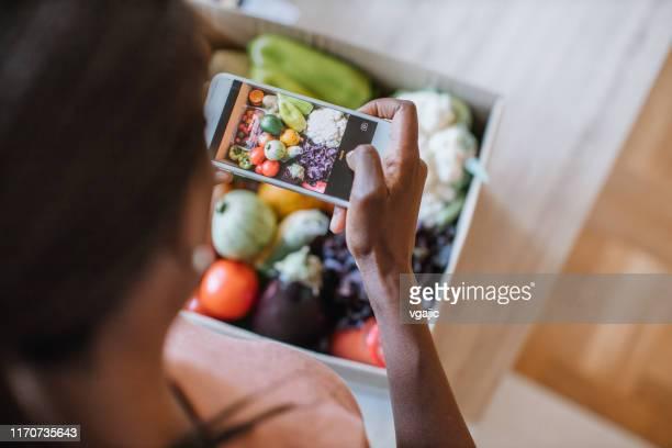woman photographing groceries in meal kit - fotografar imagens e fotografias de stock