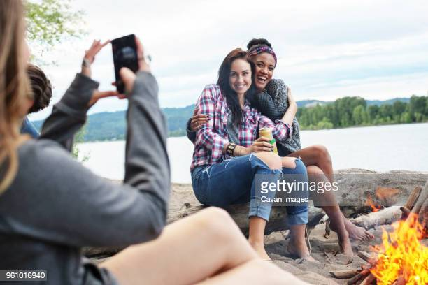 Woman photographing happy female friends sitting on tree trunk by campfire against river