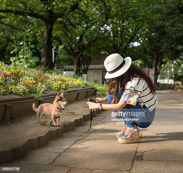 Woman photographing her dog with smartphone.
