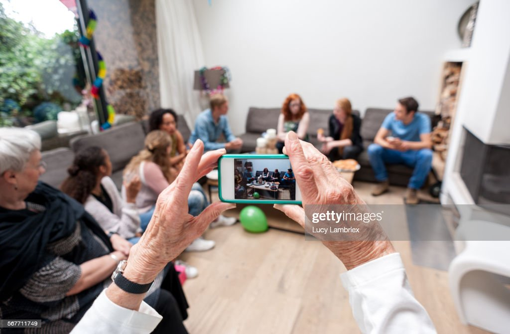 Woman photographing her family : Stock Photo