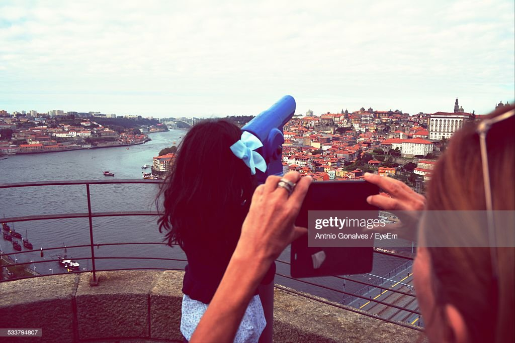 Woman Photographing Her Friend, Cityscape In Background : Foto stock