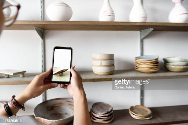 woman photographing her products for sale - 人工物 ストックフォトと画像