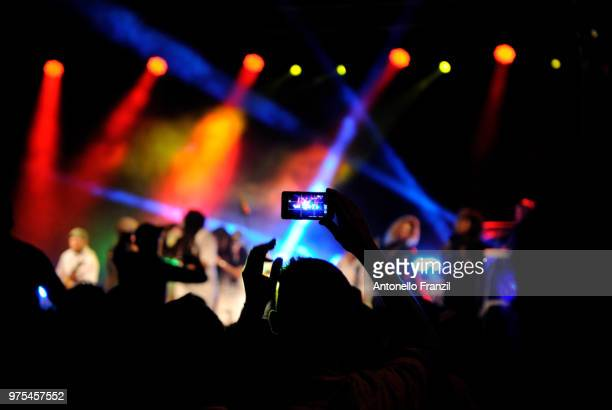 woman photographing in pop concert, sardinia, italy - reggae stock photos and pictures