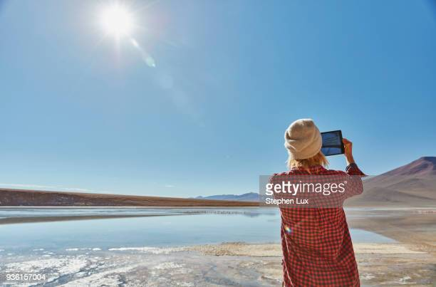 Woman photographing landscape, using digital tablet, Salar de Chalviri, Chalviri, Oruro, Bolivia, South America